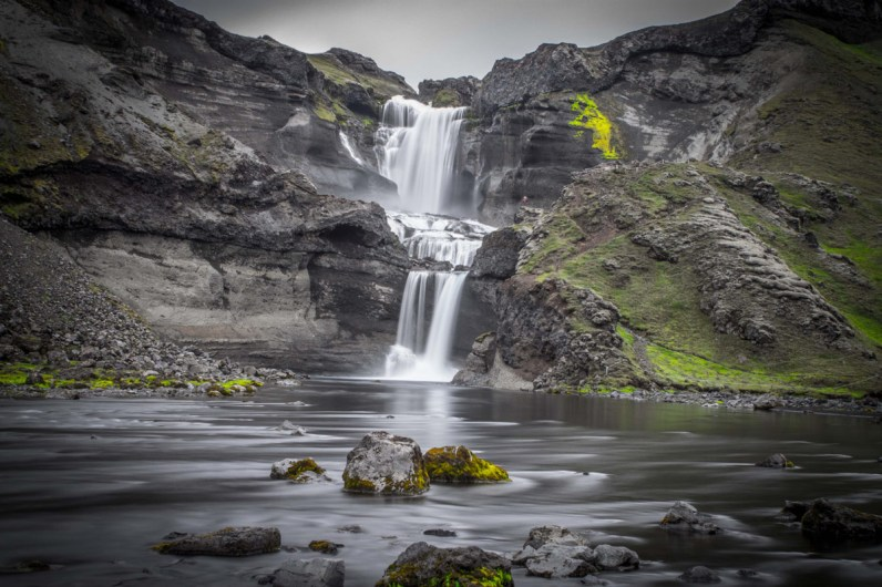 Ofaerufoss waterfall cascades among black rock and bright green grass into Eldja Canyon in Iceland