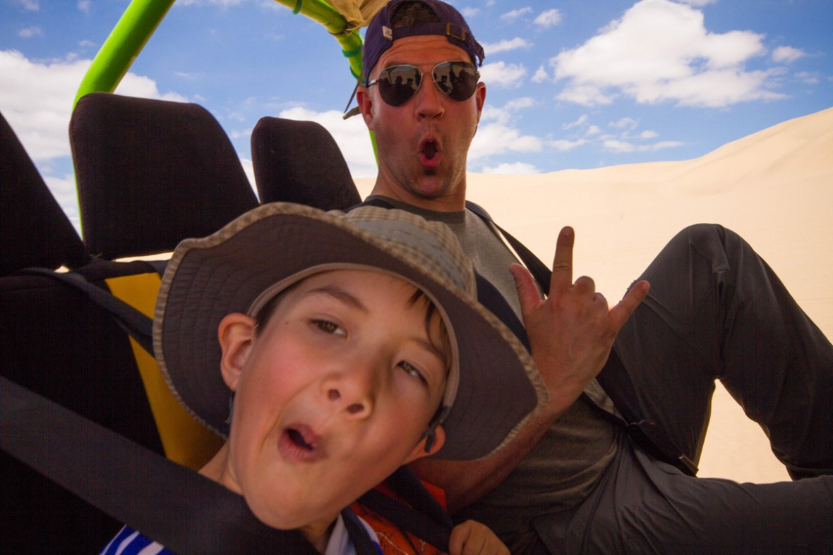 A father and son celebrate while riding in a dune buggy through the desert as they prepare to go sandboarding with kids in Peru in the desert near Huacachina Peru