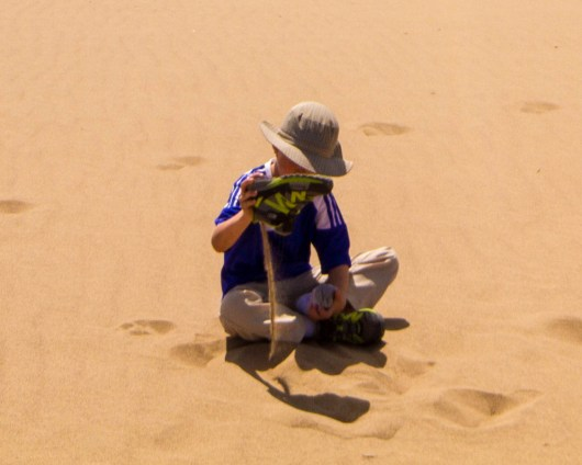 A young boy pours sand from his shoes in the desert after sandboarding with kdis in Peru