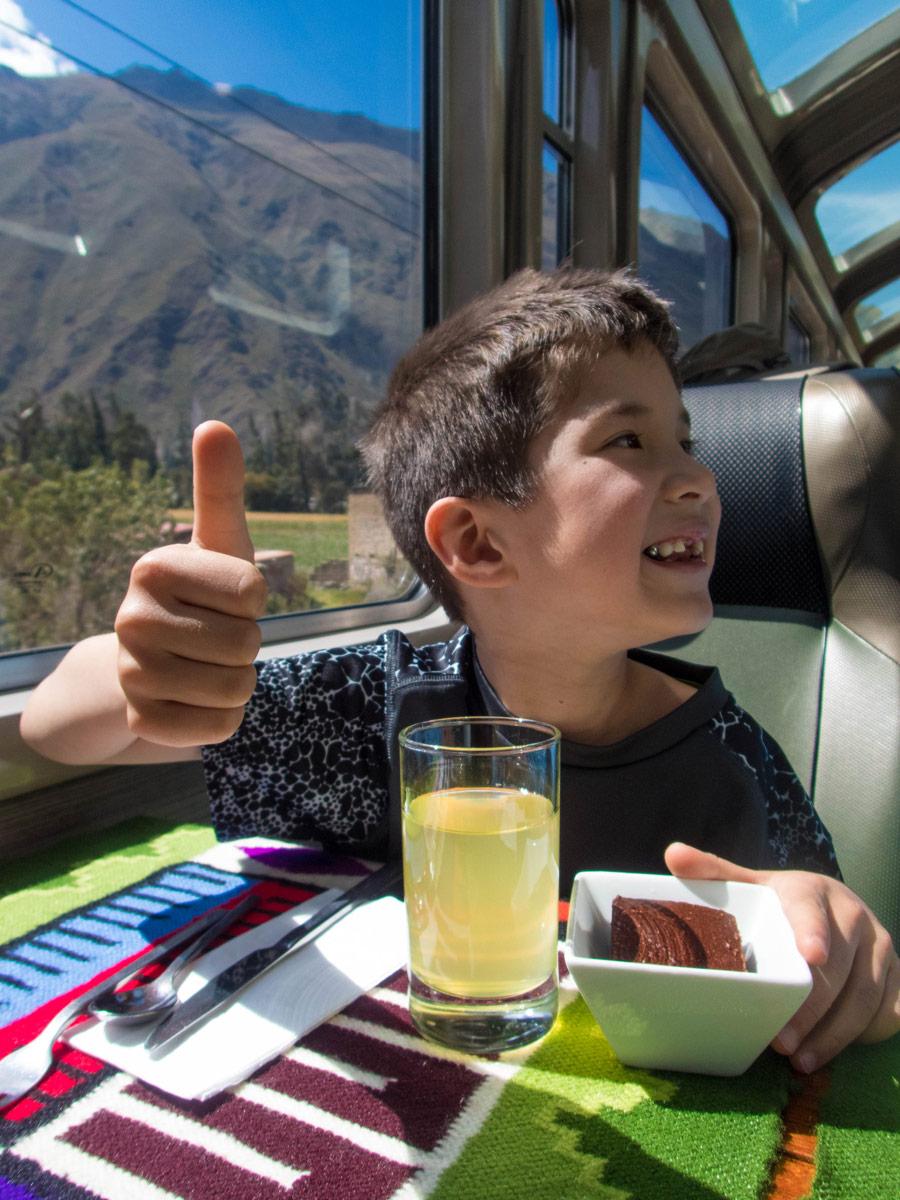 Machu Picchu with kids - Boy enjoying the chocolate cake dessert on the Vistadome train on the way to Macchu Picchu.