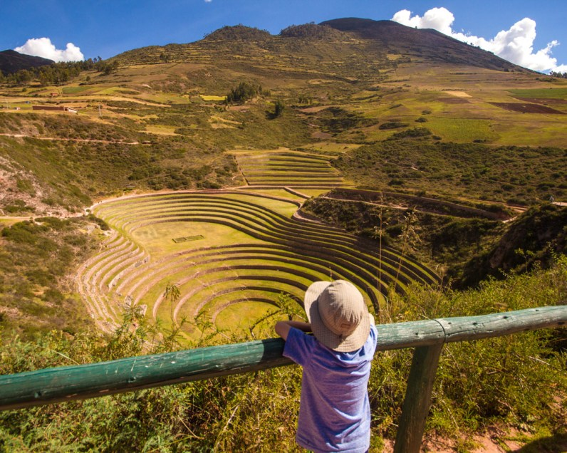 Boy looking out onto the Moray ruins in the Sacred Valley, Peru.