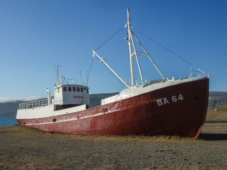 The Icelandic steelship Gardar, a red and white fishing boat, beached along the shores of Iceland's Westfjords