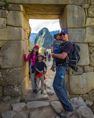 Family poses at the official end of the Inca Trail in Machu Picchu.