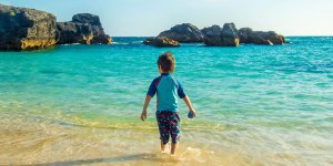A young boy wades into the waters of Horseshoe Bay Beach, the perfect place to visit in Bermuda with kids