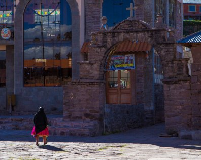 A Taquileano woman walks towards a stone arch in the islands center square, one of the things we saw while visiting Lake Titicaca with kids
