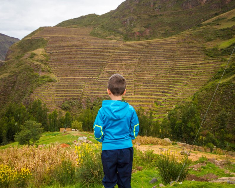 A young boy wearing a blue sweater looks out over agricultural terraces in the Sacred Valley of Peru