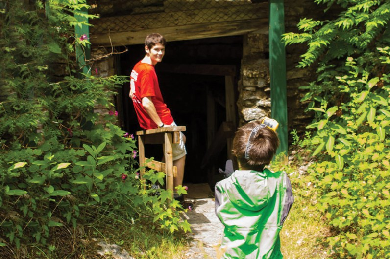 A young boy in a caving outfit walks towards a cave entrance while a guide watches him in Bonnechere caves with kids