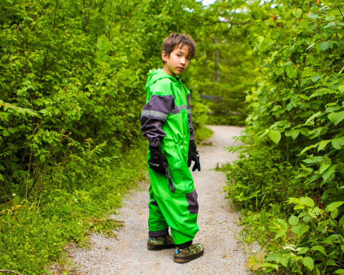 A young boy wearing a green Oakiwear caving outfit looks at the camera during a visit to Bonnechere Caves with kids