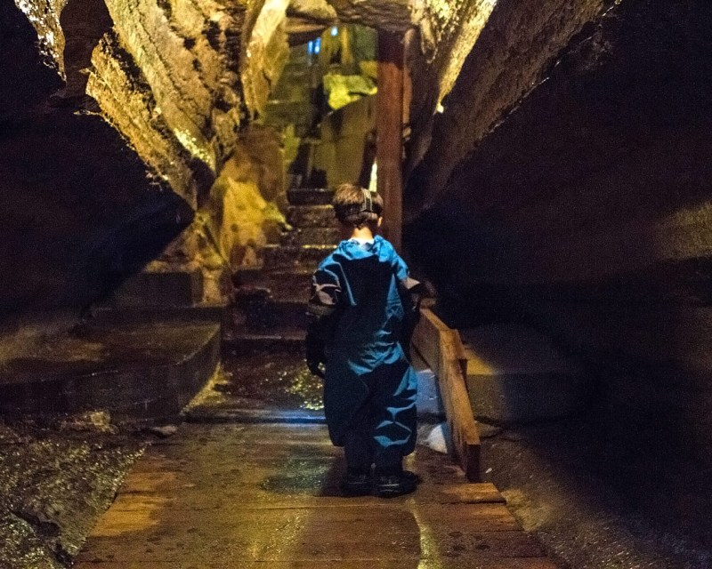 A toddler wearing a caving outfit walks alone through a show cave during a visit to Bonnechere Caves with kids