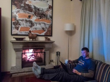 A man works on a laptop near a fireplace in the Andean Cottage of the Casa Andina Private Collection Sacred Valley Peru