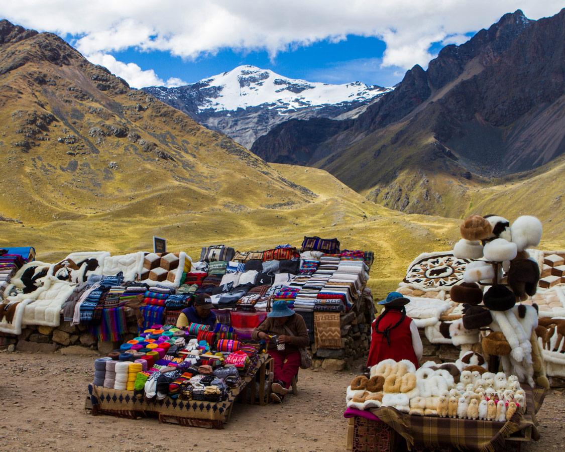 Local Quechua women sell handicrafts at a market in Abra la Raya Peru along the Cusco to Puno bus tour in Peru