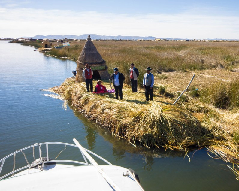 Uros people collect tickets from tour boats on Lake Titicaca Peru