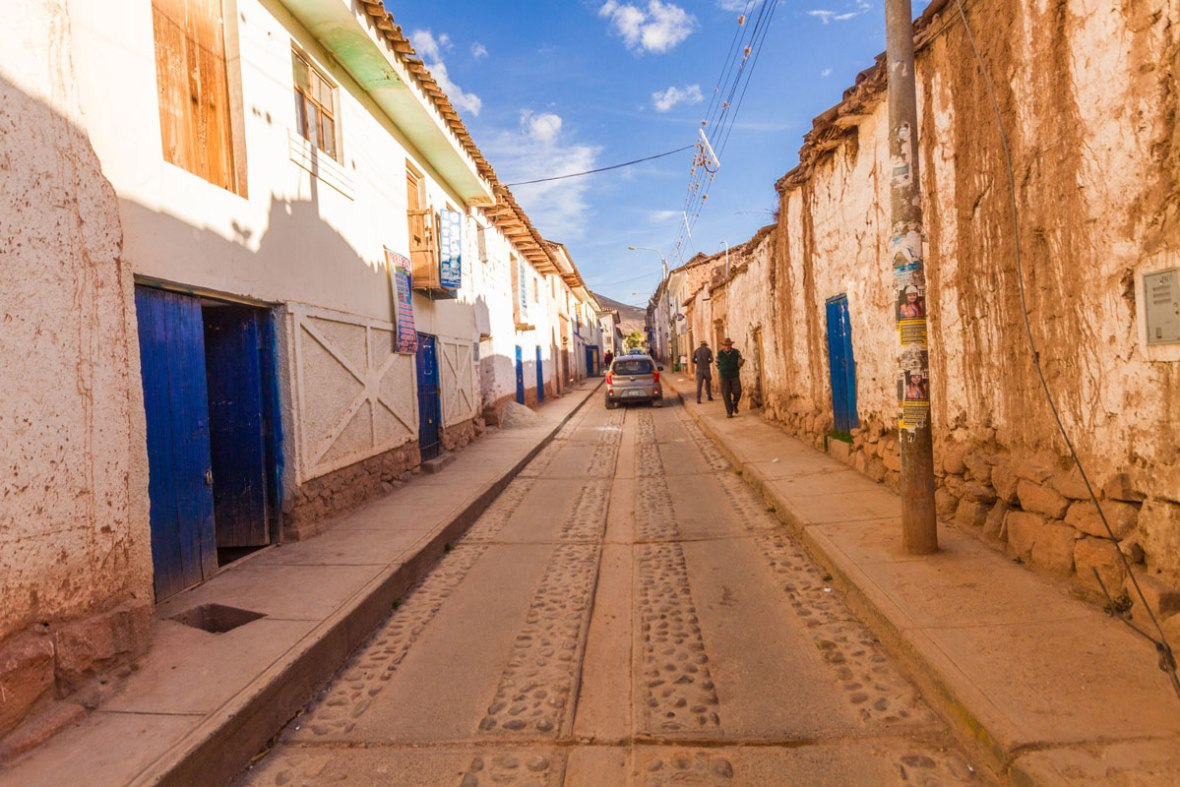 A narrow street lined with white adobe buildings with bright blue doors in Maras Peru
