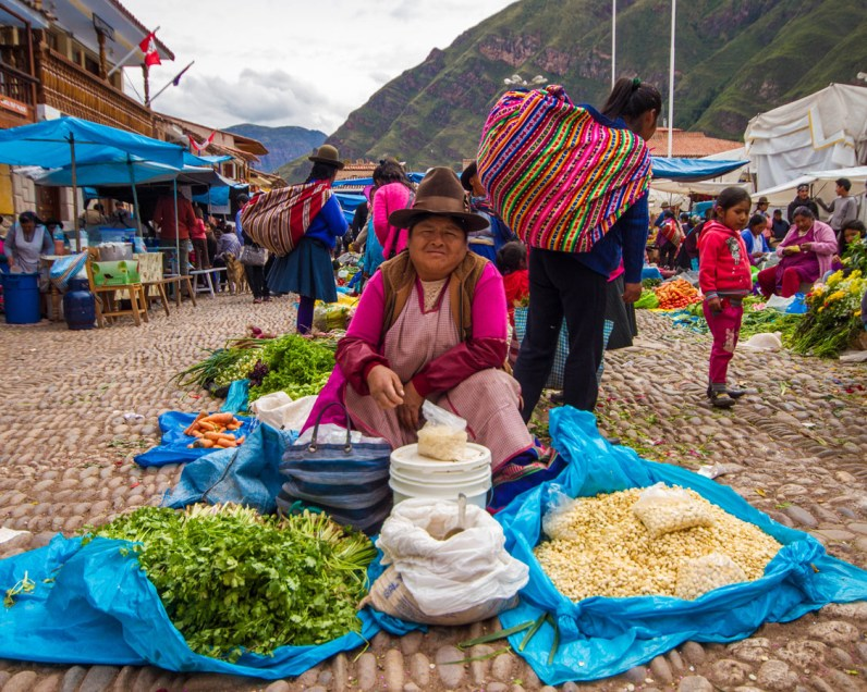 A Quechua woman wearing traditional colorful fabrics and hat sells food and grains at the Pisac Market in Peru