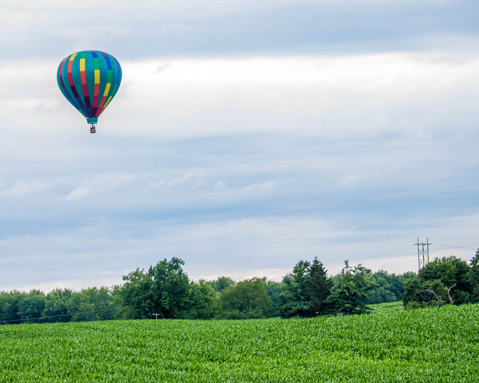 A hot air balloon rises over a field in Letchworth State Park in New York State