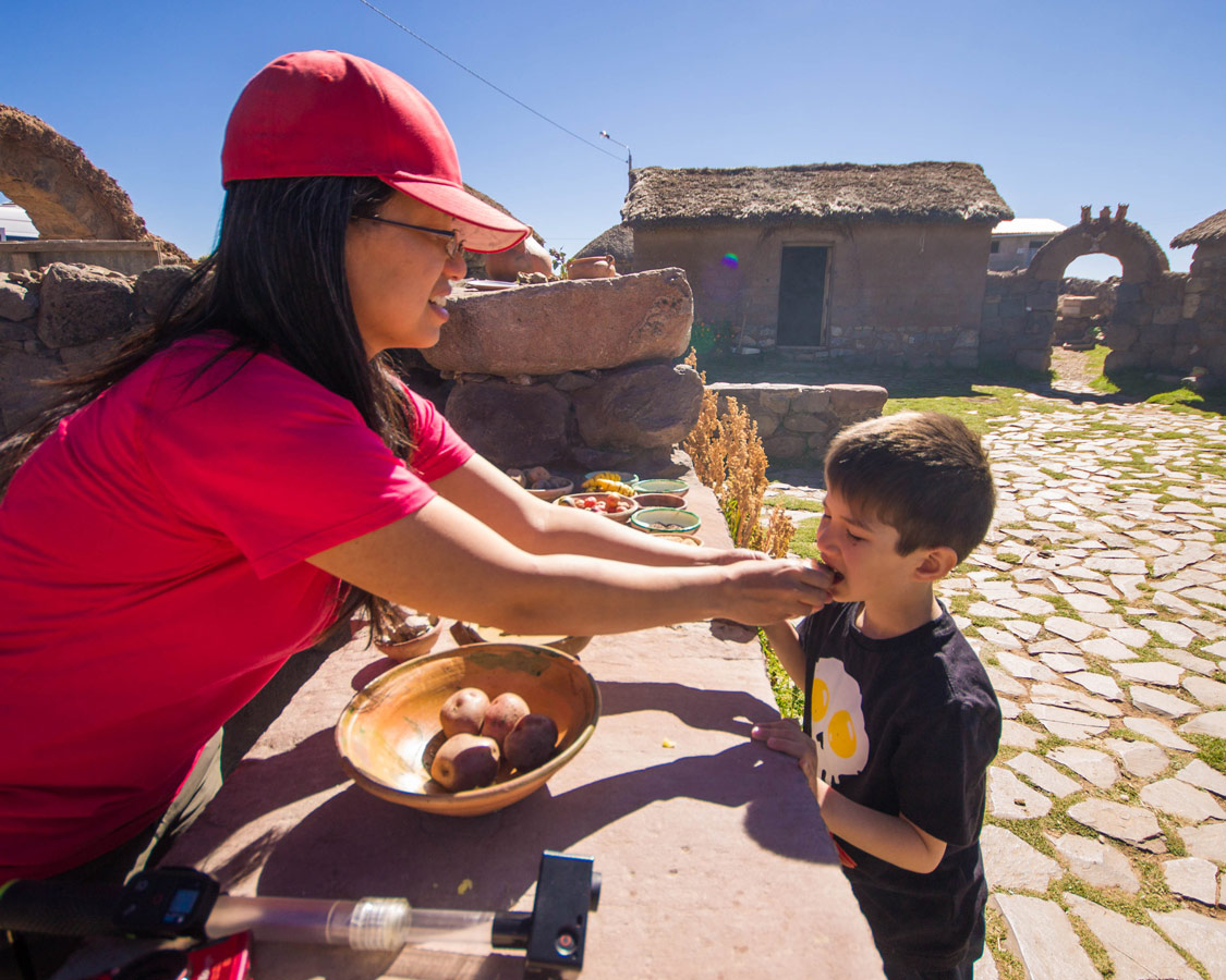 Christina Wagar gives her son a taste of potato and clay, a food said to aid stomach trouble, at a small Peruvian village near Puno on the way to see the Andean Condors in Colca Canyon with kids