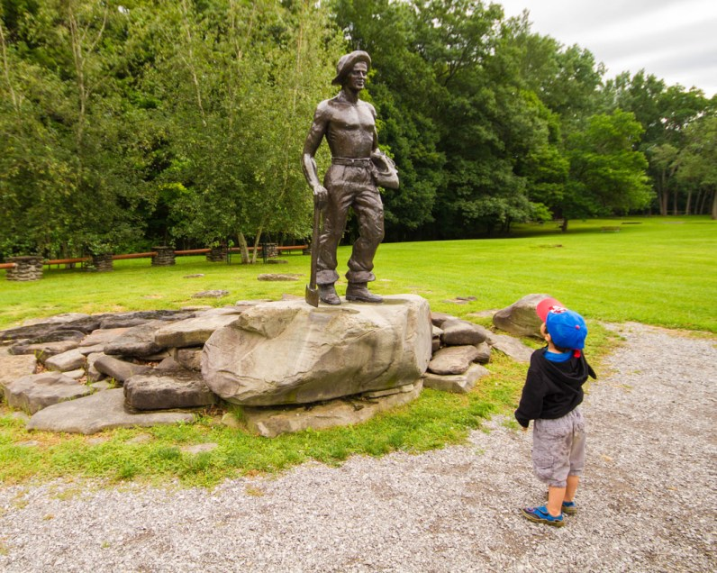 A young boy examines a statue at Letchworth State Park with kids in New York State