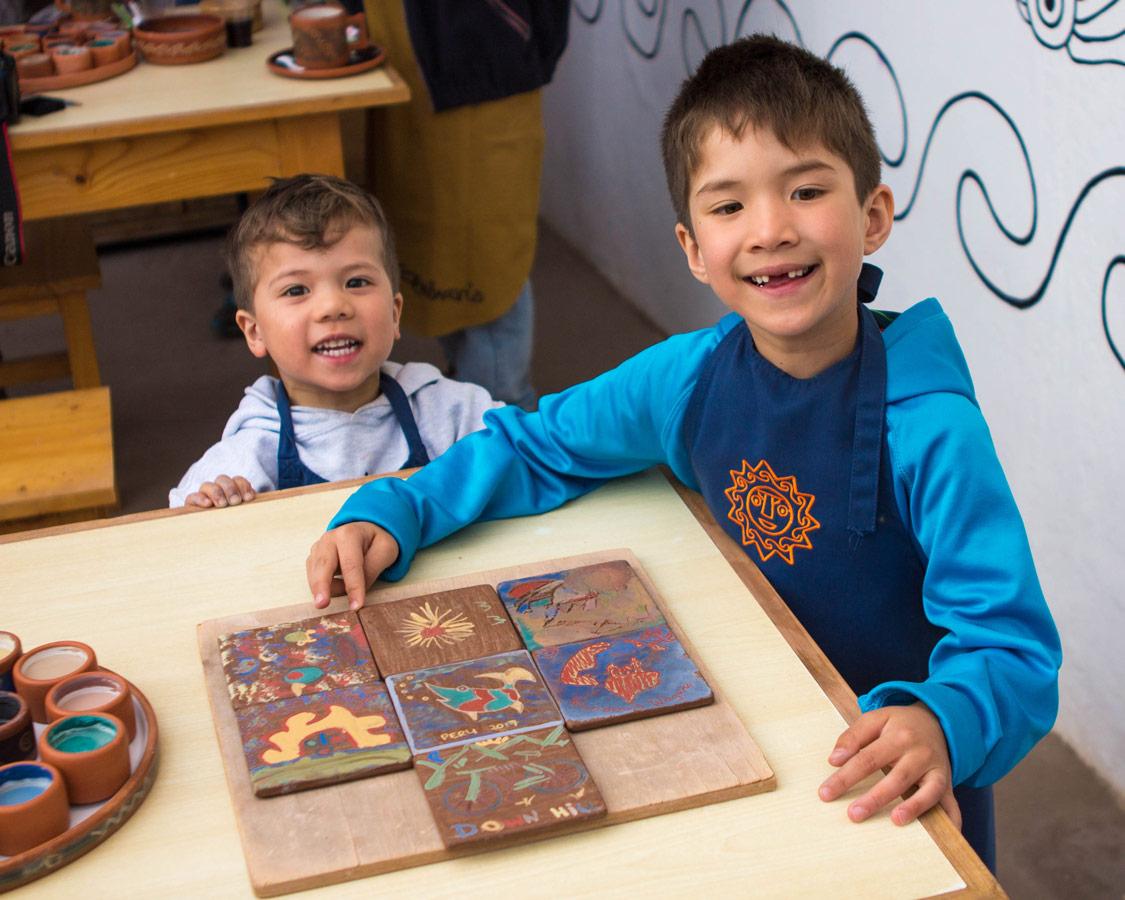 two boys show off their ceramics painting for kids art at the Pablo Seminario Urubamba Peru workshop