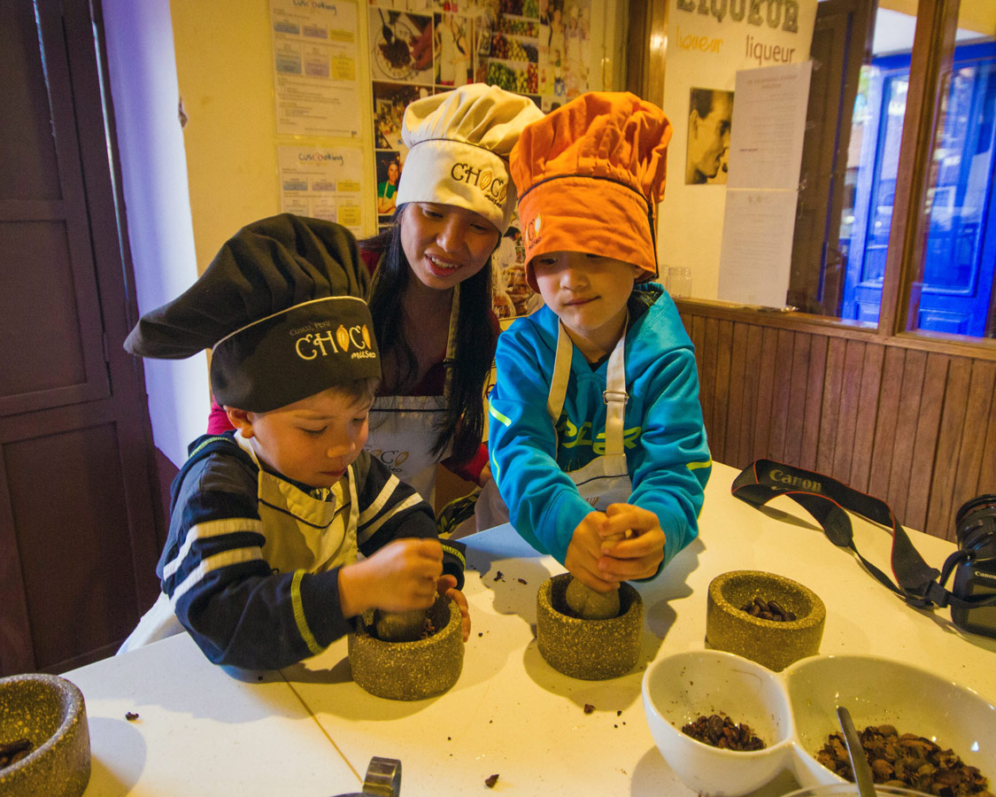Christina and the boys grind chocolate beans at the Chocomuseuo in Cusco Peru. The Chocomuseo is one of the best things to do in Cusco Peru with kids