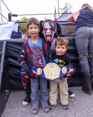 Boys pose with a professional wrestling athlete at the Bala Cranberry Festival