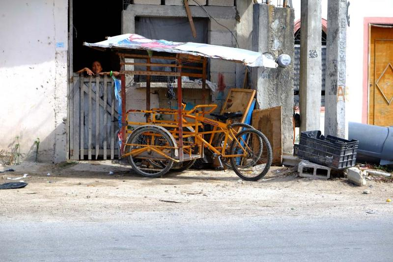 A Mexican villager looks out a window near a bike rack in Tulum Mexico