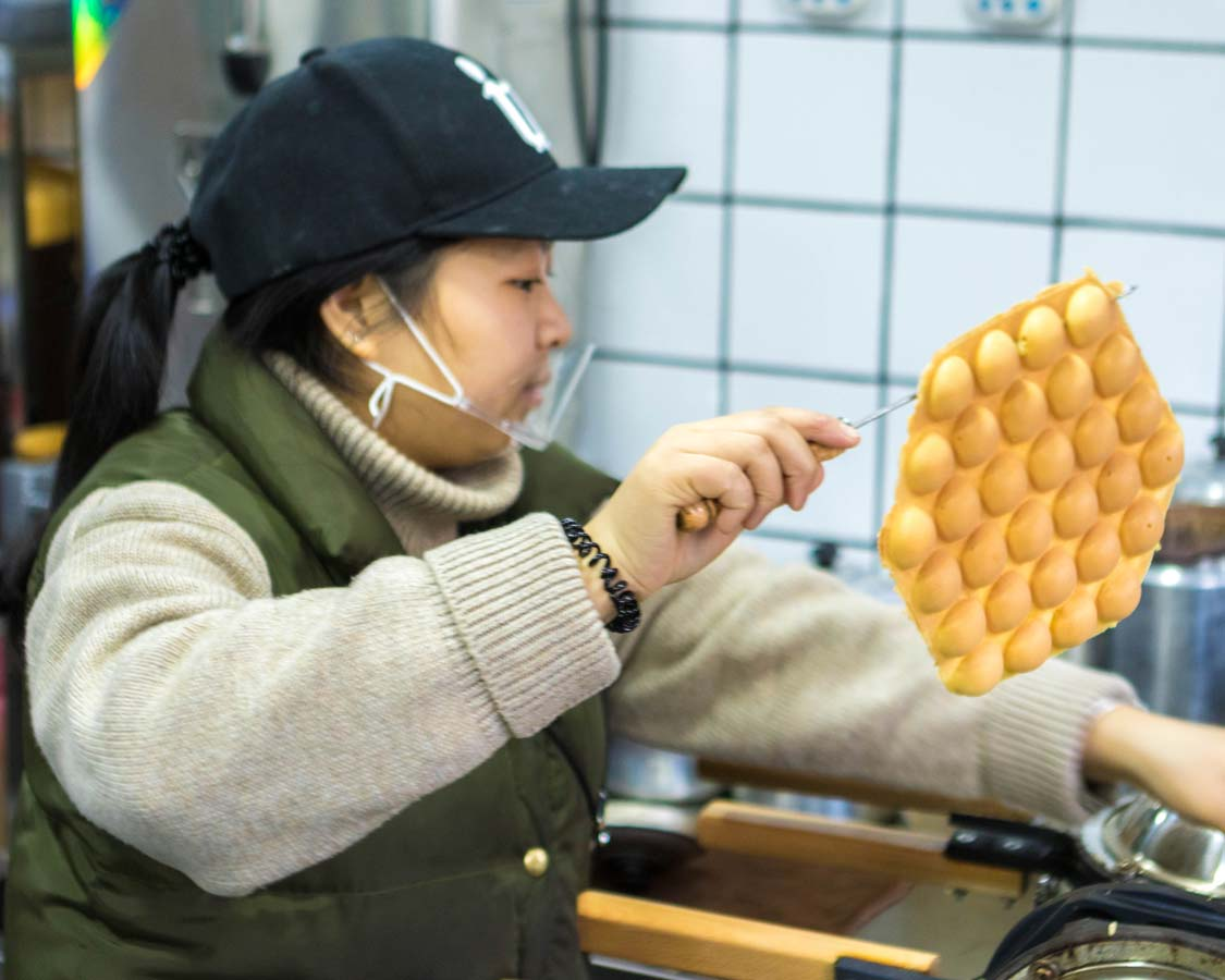A shopkeeper at Law Kong Yuen Milk Tea Shop makes Shanghai style waffles on a food tour