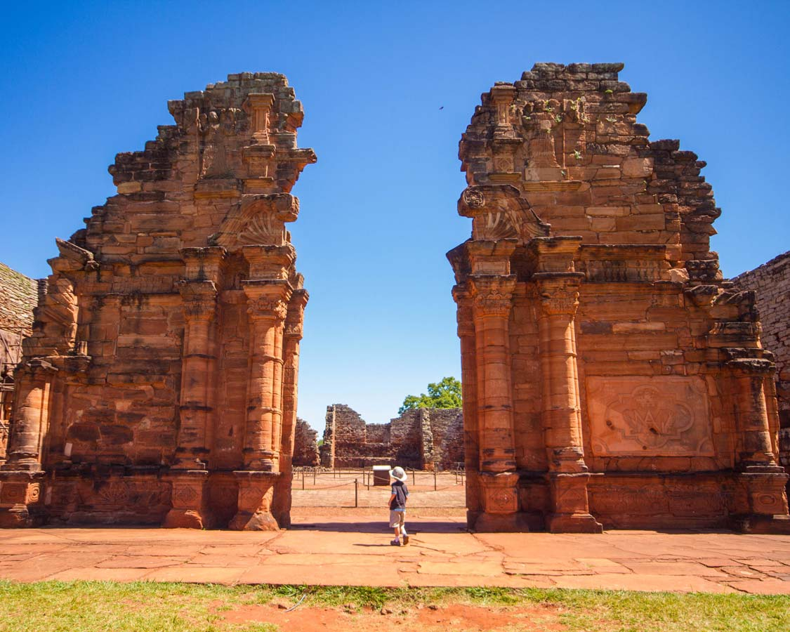 A young boy stares up at the The towering walls of the church of the Jesuit Ruins of San Ignacio Miní in San Ignacio, Argentina