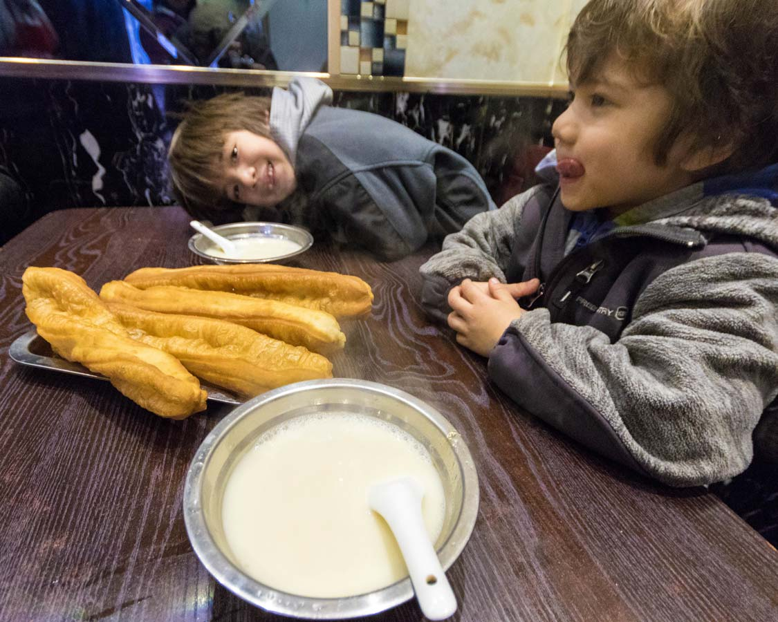 Children at a food stall in Shanghai China eating youtiao and soymilk on a Shanghai Unfood tour
