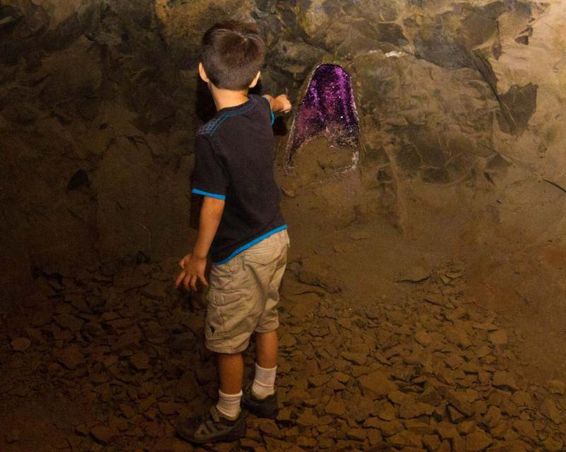 A young boy points at a purple geode in Wanda Mines near San Ignacio Argentina