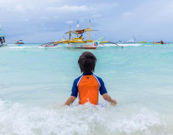 A young boy plays in the surf on Boracay Beach