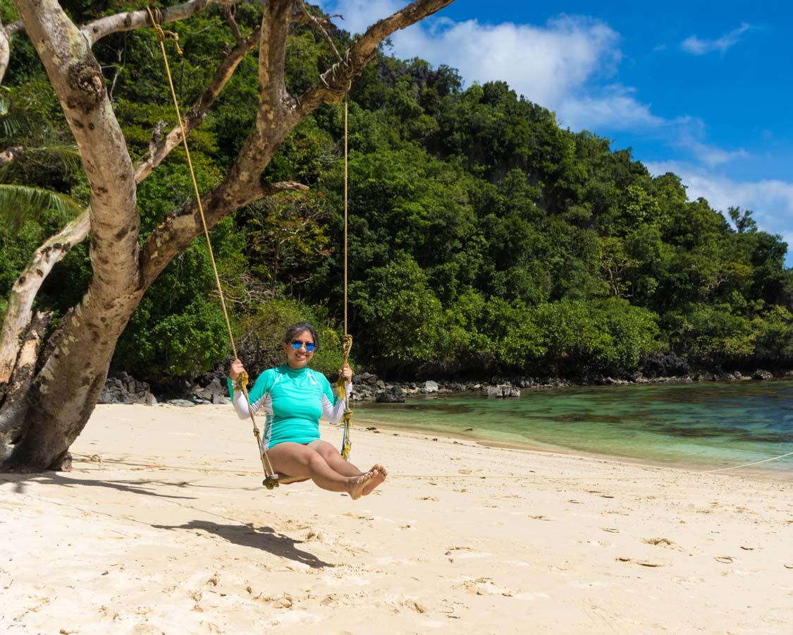 Woman on a swing at Entalula Beach in El Nido Philippines
