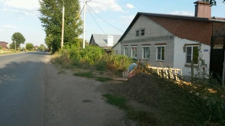 Die lange Straße zum Palast, mit einfachsten Häusern, oft Marke Eigenbau, verwilderten Hecken und fehlenden Gehsteigen. Ein typisches Außenviertel von Kazan.