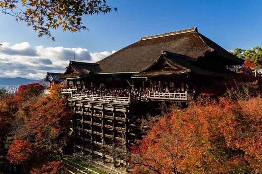 View of the front facade of Kiyomizu-dera temple in Kyoto on a sunny autumn day.