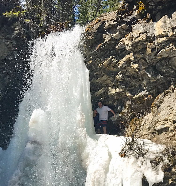 An image of a couple peaking out from behind Troll Falls in Kananaskis, Alberta