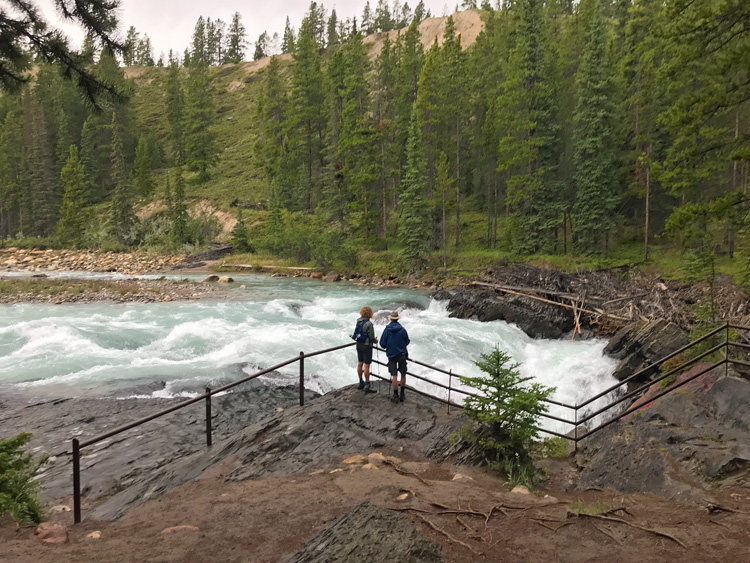 An image of a couple overlooking the top of Siffleur Falls in Alberta, Canada.