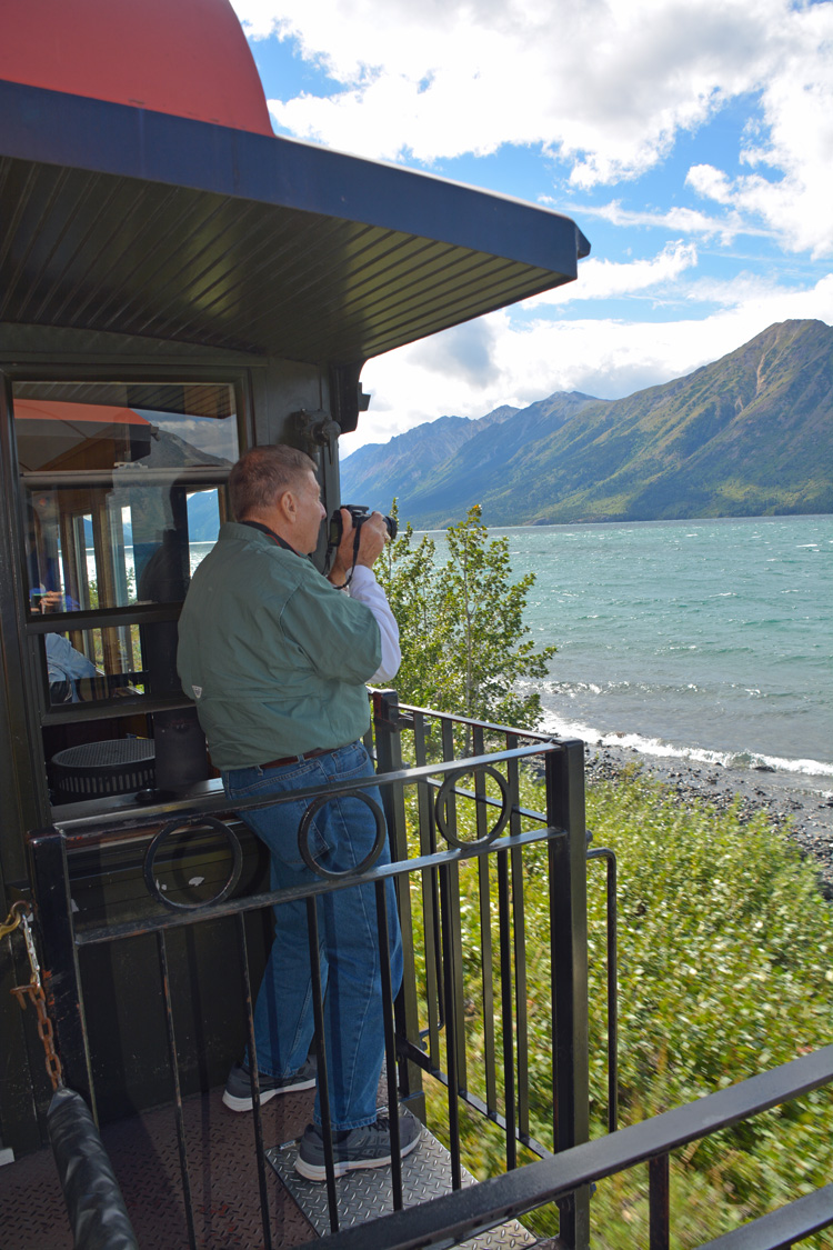 An image of a man taking a photo from the back of the White Pass rail car