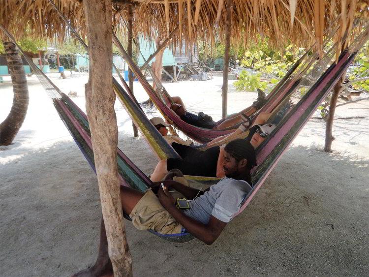 Four people relaxing in hammocks in Belize