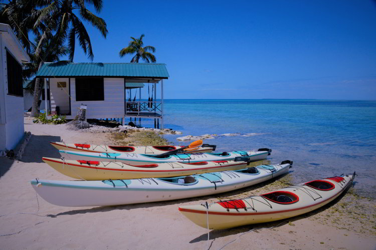An image of four kayaks on the beach at Tobacco Caye Paradise Resort in Belize