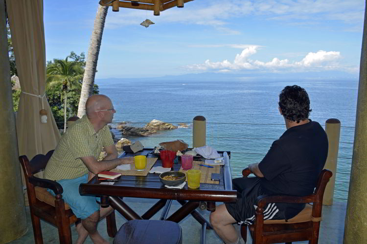 An image of two men sitting at a dining table and looking at the view at Casa Pericos in Yelapa - Jalisco, Mexico - Yelapa Beach
