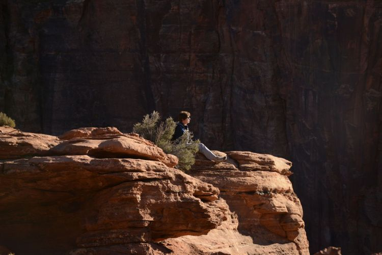 An image of the author sitting on a cliff watching the sunset at Canyon Overlook in Zion National Park in Utah - Best Zion National Park Hikes