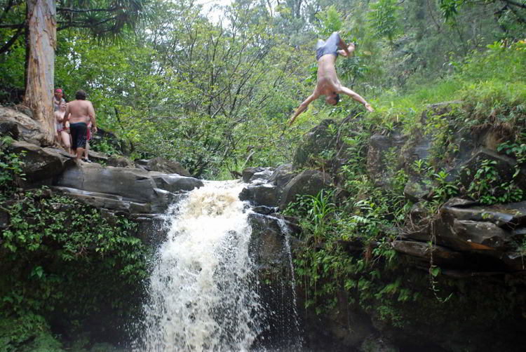 An image of a diver flipping above Twin Falls on the island of Maui, Hawaii - Hiking Maui