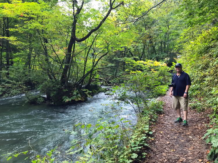 An image of a man standing on the trail beside Oirase Stream near Aomori, Japan - Lake Towada and Oirase Gorge