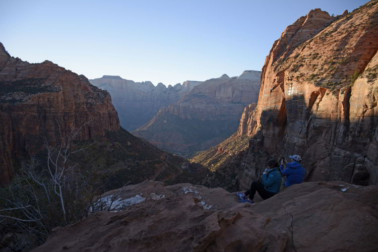 An image of two people sitting on the cliffs a sunset at Canyon Overlook in Zion National Park in Utah - Best Zion National Park Hikes