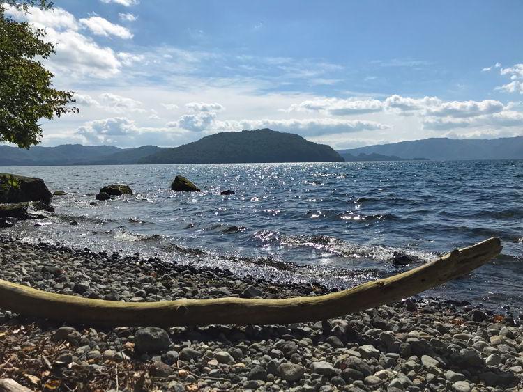An image of the sun reflecting off of Lake Towada near Aomori, Japan - Lake Towada and Oirase Gorge