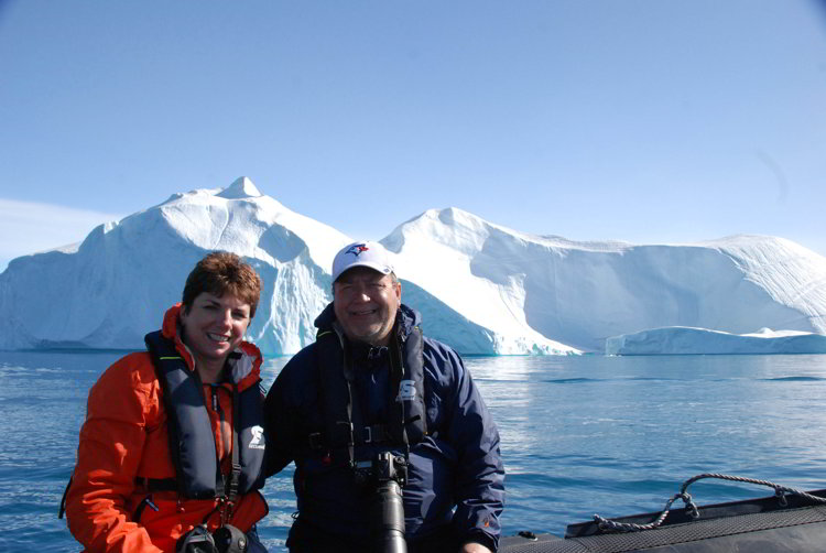 Two people sitting on a zodiac with an iceberg behind them near Ilulissat Greenland
