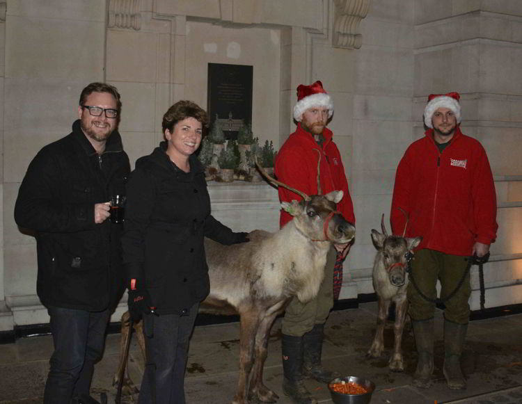An image of four people posing with two reindeer at the Covent Garden Market in London, UK - Europe's Best Christmas Markets
