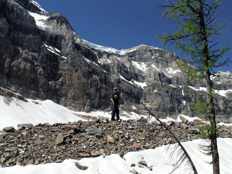 An image of a man standing on a rocky moraine in the backcountry of Banff National Park - Shadow Lake Lodge