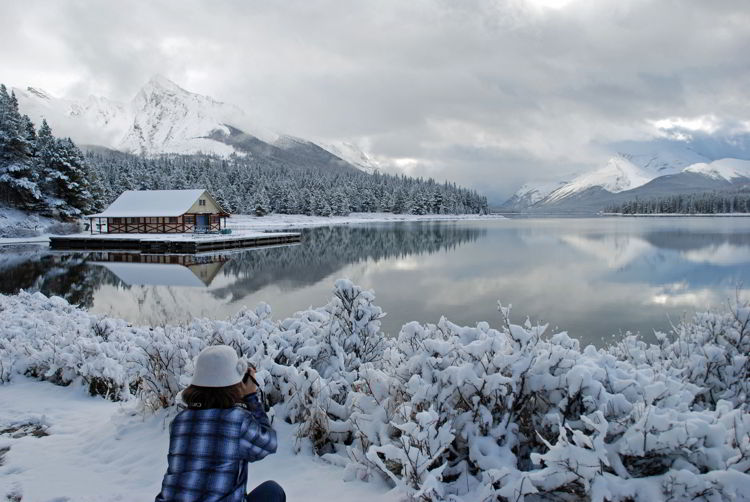 An image of a woman taking a photograph of Maligne Lake with snow on the ground, but the lake unfrozen. Jasper in winter - stunning photos