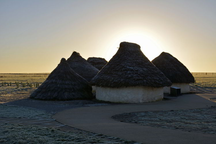 An image of the sunrise over the reconstructed Neolithic houses at the Stonehenge site near Salisbury, UK - Stonehenge inner circle tours