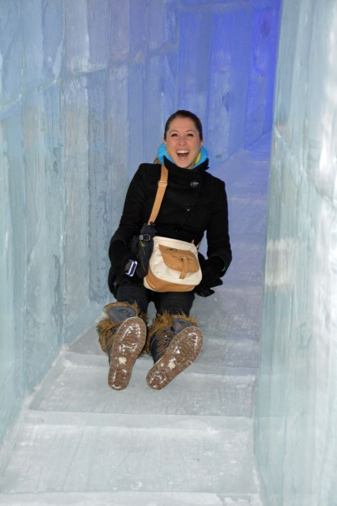 An image of a woman sliding down an ice slide inside the Hôtel de Glace in Quebec, Canada - Ice Hotel Quebec